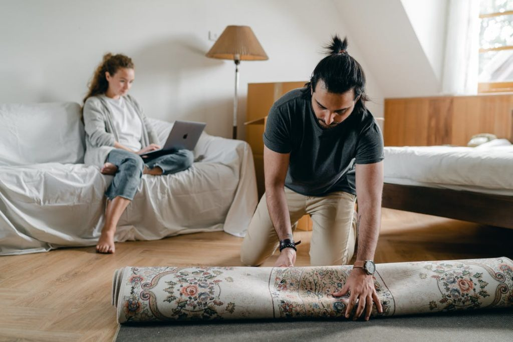 Fit ethnic male in wristwatch laying carpet on parquet while barefoot woman browsing internet on portable computer sitting on cozy sofa in bedroom